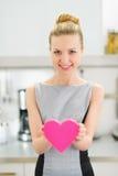 Femme au foyer montrant le coeur décoratif dans la cuisine Image stock