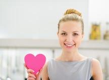 Femme au foyer montrant le coeur décoratif dans la cuisine Photos libres de droits