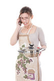 Femme au foyer nerveuse dans le tablier tenant le pot et parlant sur le mobile Photographie stock libre de droits