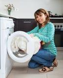 Femme au foyer ordinaire à l'aide de la machine à laver Photographie stock