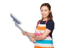 Femme au foyer se tenant avec du solvant de vide Photo stock