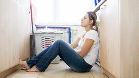 Femme au foyer seule bouleversée s'asseyant sur le plancher après avoir fait la blanchisserie image stock