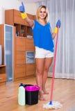 Femme au foyer souriant et faisant le plancher nettoyant à l'intérieur Photos libres de droits