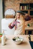 Femme au foyer tenant la po?le et la spatule en bois photo libre de droits