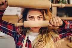 Femme au foyer tenant les goupilles en bois dans des mains image stock