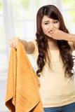Femme au foyer tenant une blanchisserie de mauvaise odeur photographie stock
