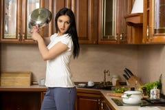 Femme au foyer tenant une casserole Il se tient dans la cuisine Images stock