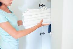 Femme au foyer tenant une pile de linge de lit lavé vêtements et toile de lavage, blanchiment des choses blanches photo stock