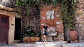 Femme au poste d'eau potable images libres de droits