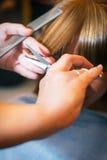 Femme au salon de beauté redressant des cheveux Image stock