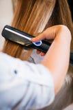 Femme au salon de beauté redressant des cheveux Photo stock