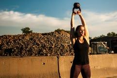 Femme au sommet d'oscillation de cloche de bouilloire Images stock