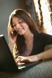 Femme au téléphone utilisant l'ordinateur image libre de droits