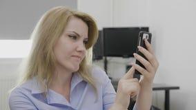 Femme au travail utilisant le smartphone pour des achats en ligne sur l'Internet montrant différentes grimaces et réactions tandi banque de vidéos