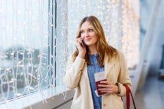 Femme au vol de attente d'aéroport international Photographie stock libre de droits