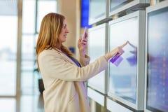 Femme au vol de attente d'aéroport international Photo stock