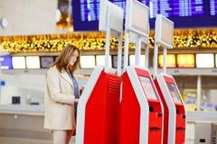 Femme au vol de attente d'aéroport international Photos libres de droits