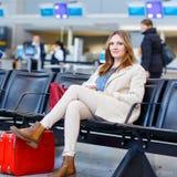 Femme au vol de attente d'aéroport international sur le terminal Photos stock