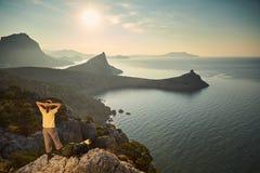 Femme augmentant des montagnes et regardant le coucher du soleil Images stock