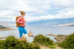 Femme augmentant la marche avec le chien sur la traînée de bord de la mer Image stock