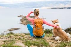 Femme augmentant la marche avec le chien sur le paysage de mer Images stock