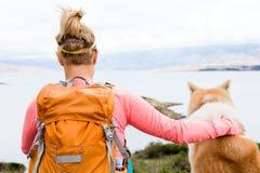 Femme augmentant la marche avec le chien sur le paysage de mer Image libre de droits