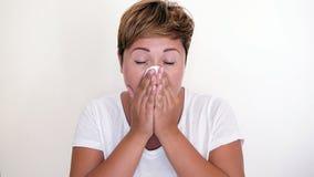 Femme aux cheveux courts soufflant son nez sur le fond blanc Photo libre de droits