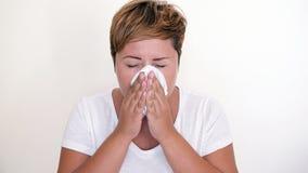 Femme aux cheveux courts soufflant son nez sur le fond blanc Photographie stock libre de droits