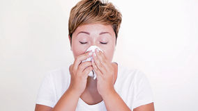 Femme aux cheveux courts soufflant son nez sur le fond blanc Image stock