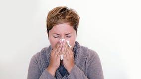 Femme aux cheveux courts utilisant un chandail soufflant son nez Photographie stock libre de droits