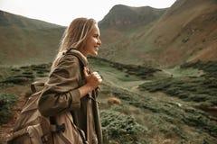 Femme aux cheveux longs souriant heureusement tout en étant dans les montagnes image libre de droits