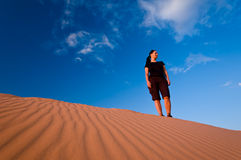Femme aux dunes de sable roses de corail Image stock