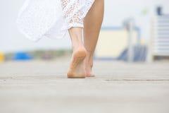 Femme aux pieds nus d'angle faible marchant loin Images stock