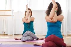 Femme aux pieds nus du jeune Caucasien deux s'asseyant faisant l'exercice de yoga photo stock