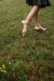 Femme aux pieds nus marchant sur l'herbe Photo stock