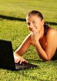 Femme aux pieds nus sur l'herbe et l'ordinateur portatif Image libre de droits