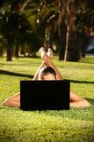 Femme aux pieds nus sur une herbe avec un ordinateur portatif Photos libres de droits
