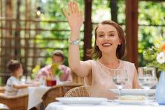 Femme aux yeux noirs de sourire soulevant sa main appelle la serveuse Photographie stock