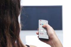 Femme avec à télécommande devant la TV Images stock