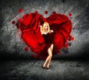 Femme avec éclabousser le coeur sur le fond foncé Image libre de droits
