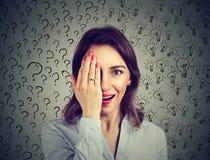 Femme avec beaucoup d'ampoules d'idée de questions et réponses couvrant la moitié de son visage de main Photographie stock