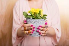 Femme avec de beaux anneaux tenant la fleur photographie stock libre de droits