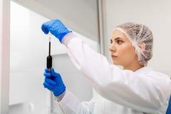Femme avec de l'acide sulfurique dans le compte-gouttes au laboratoire image libre de droits