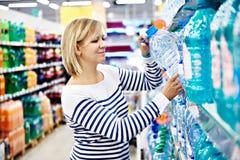 Femme avec de l'eau potable de bouteille dans la boutique images stock