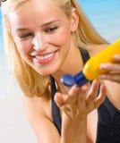 Femme avec de la crème de soleil-protection Photos stock