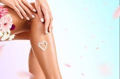 Femme avec de la crème sur sa jambe et bouquet de fleurs Photo libre de droits