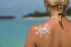 Femme avec de la crème soleil-formée du soleil Photo stock