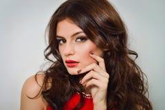 Femme avec de longs cheveux bruns de beauté et lèvres rouges dans la robe rouge Image stock
