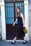 Femme avec de longs cheveux portant une robe noire avec des conceptions florales photo stock