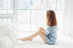 Femme avec de longs cheveux rouges se reposant dans le lit par la fenêtre avec la vue de ville, s'étendant après s'être réveillé images stock